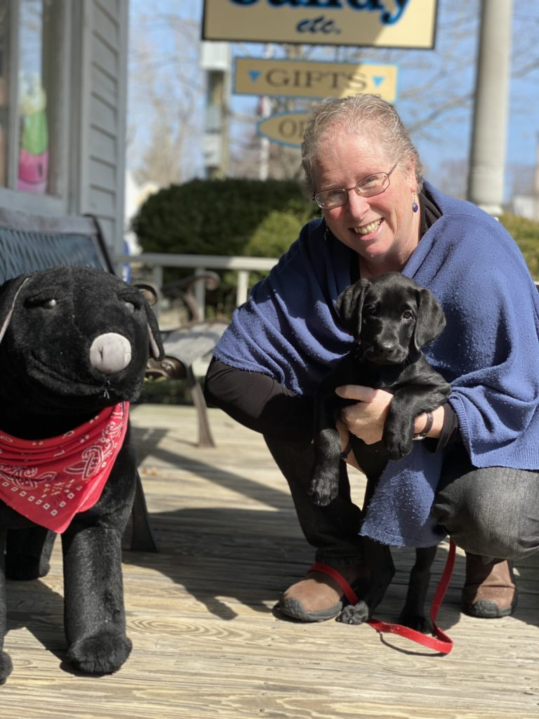 Owner Nancy Magunuson and her puppy Flicka on the porch of Nancy's Candy Etc.
